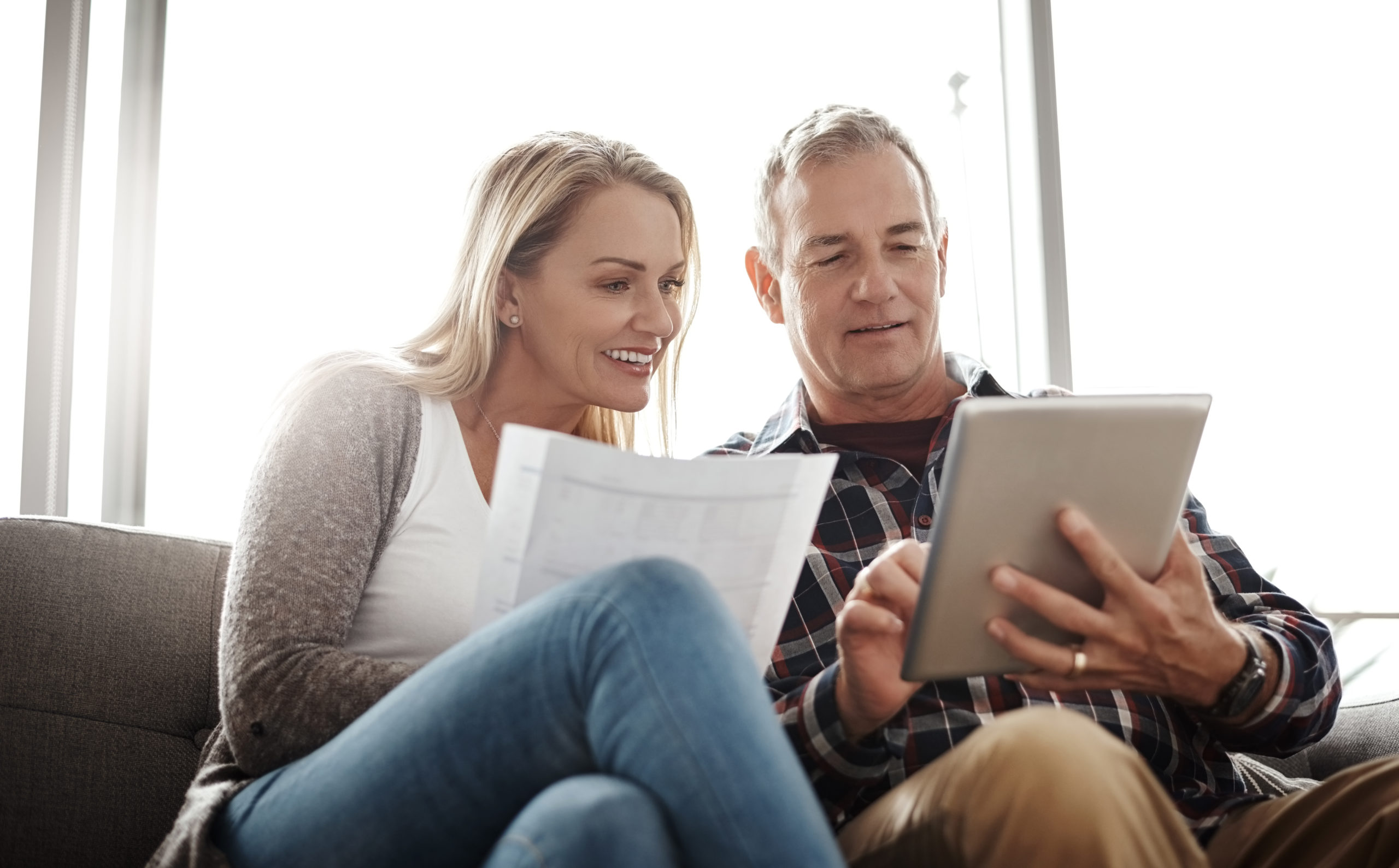 Shot of a mature couple using a digital tablet while going through their paperwork together on the sofa at home